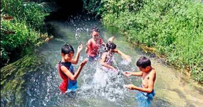 Çocuklar kanalda yüzerek serinledi