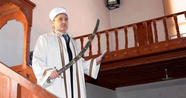 O camide imam hutbeyi kılıçla okuyor