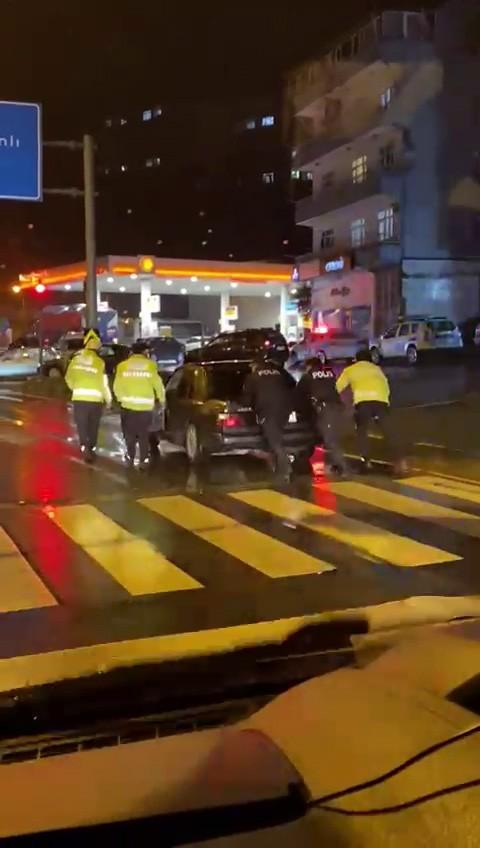 Trafik polisi yolda kalan otomobili iterek, sürücüye yardım etti